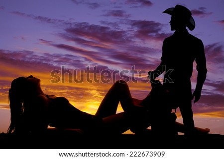 A silhouette woman laying back with her cowboy standing. - stock photo