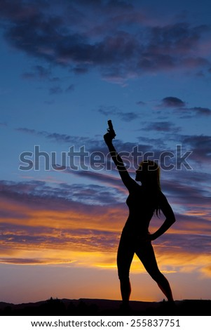 a silhouette woman pointing her pistol in the air in the outdoors. - stock photo