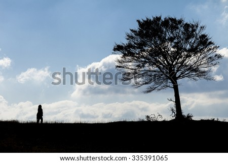 A silhouette woman walking to  a silhouette tree. Blue sky with clouds background - stock photo