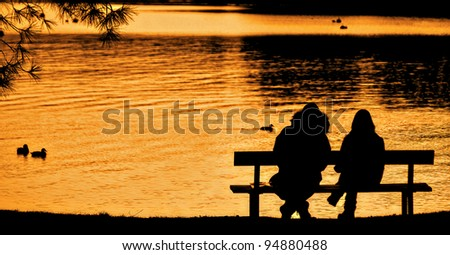 a silhouetted couple sitting on a lakeside bench enjoying the sunset over the lake - stock photo