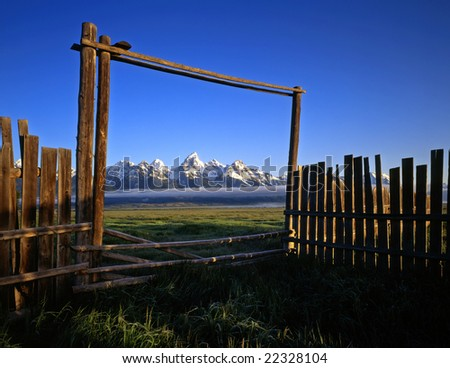 A silhouetted fence, gate and Teton Mountain Range, on an old homestead, in Grand Teton National Park, Wyoming. - stock photo