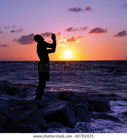 A silhouetted man stands with hands folded in praise - stock photo