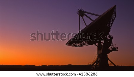 A silhouetted radio telescope, part of the Very Large Array (VLA), in New Mexico. - stock photo