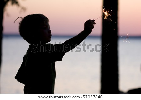 A sillouhette of a young boy holding a sparkler. - stock photo