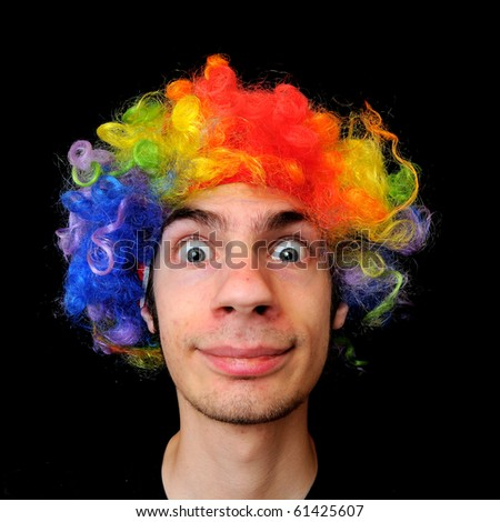 A silly crazy man wearing a clown wig with rainbow colors - stock photo