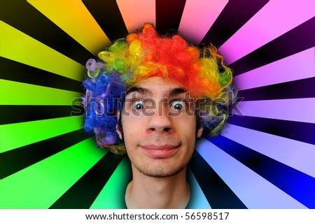A silly crazy man wearing a clown wig with rainbow colors behind him - stock photo