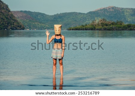 A silly young woman wearing a paper bag over her head is standing on a tropical beach and is waving - stock photo