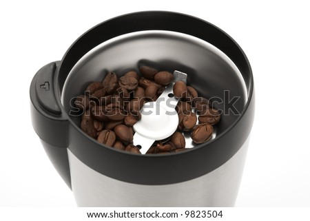 A silver and black coffee grinder with coffee beans in the grinder.  The image is isolated on white