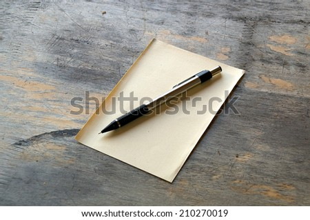 A silver and black mechanical pencil on a sheet of yellow manila paper on a distressed wooden table. - stock photo