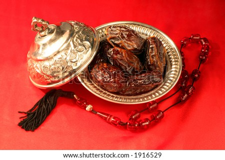A silver bowl containing the finest dates, which are traditionally eaten in Arabia for Iftar to break the Ramadan fast at sundown, next to prayer beads. - stock photo