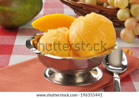 A silver bowl of mango sherbet or sorbet on a picnic table - stock photo