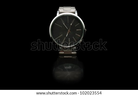A silver coloured stainless steel watch for men on black background