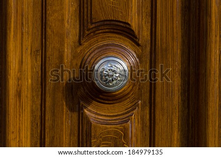 A silver door knob on a brown door - stock photo