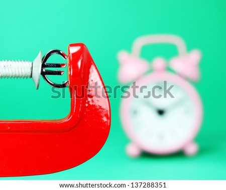 A silver Euro symbol placed in a red clamp with a pastel green background, with a pink alarm clock in the background indicating the pressure on the Euro. - stock photo