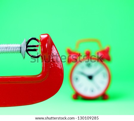 A silver Euro symbol placed in a red clamp with a pastel green background, with a red alarm clock in the background indicating the pressure on the pound sterling. - stock photo