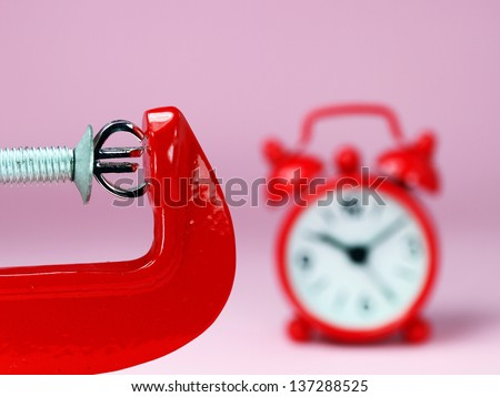 A silver Euro symbol placed in a red clamp with a pastel pink background, with a red alarm clock in the background indicating the pressure on the Euro. - stock photo