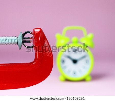 A silver Euro symbol placed in a red clamp with a pink background, with a green alarm clock in the background indicating the pressure on the pound sterling. - stock photo