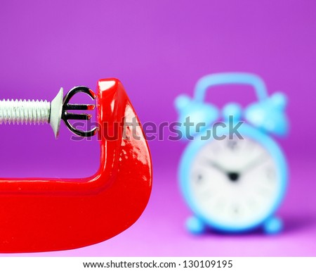 A silver Euro symbol placed in a red clamp with a purple background, with a blue alarm clock in the background indicating the pressure on the pound sterling. - stock photo