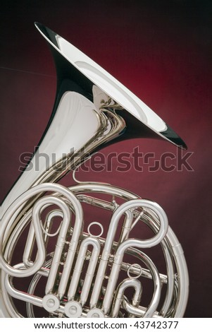 A silver French horn isolated against a spotlight red background in the vertical format. - stock photo