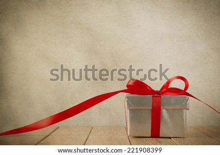 A silver gift box with red ribbon on wood plank table.  Ribbon trails off to the side and faces front.  Old grungy parchment effect gives a vintage feel.  Copy space above and on ribbon. - stock photo