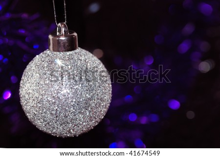 A silver glittery Christmas tree bauble, with purple and blue tinsel in the background. - stock photo