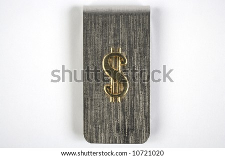 A silver money clip with a gold dollar sign on it. - stock photo