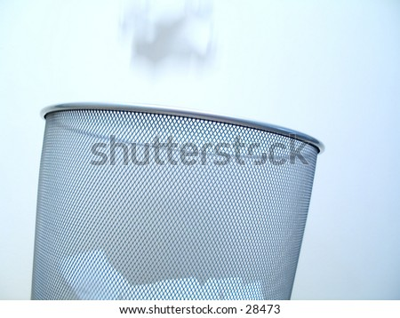 A silver pattered garbabe can close up filled with white balls of paper. A ball of paper is falling into the can (motion blur) - stock photo