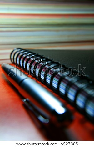 A silver pen next to a black notebook. - stock photo