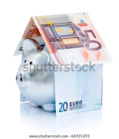 A silver piggy bank and euro bills folded in the shape of a house. - stock photo