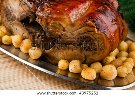 A silver Plate with a big piece of italian porchetta and new potatoes