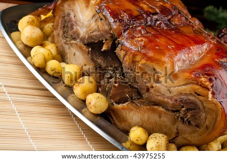A silver Plate with a big piece of italian porchetta and new potatoes - stock photo