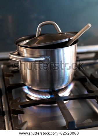 A  silver pot on a cook top under heat - stock photo
