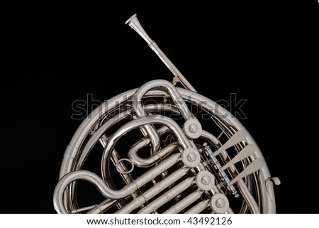 A silver professional French horn isolated against a black background with copy space. - stock photo