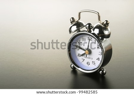 a silver retro alarm bell on black background - stock photo