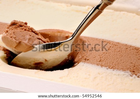 A silver spoon scooping out chocolate and vanilla ice cream - stock photo