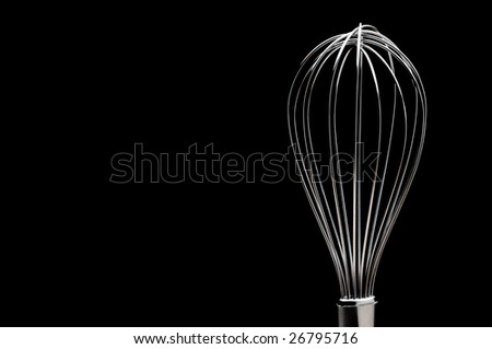A silver stainless steel whisk on a black background - stock photo