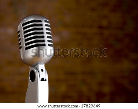 A silver vintage microphone in front of a blurred red brick wall with copy space