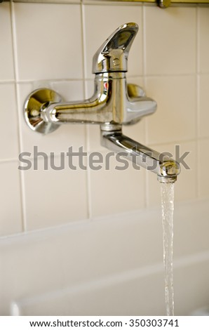 a silver water tap in the bathroom - stock photo
