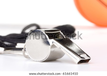 A silver whistle laying in front of an orange basketball. - stock photo