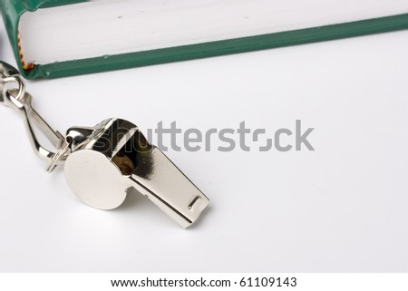 A silver whistle laying next to a green notebook. Add your text to the background. - stock photo