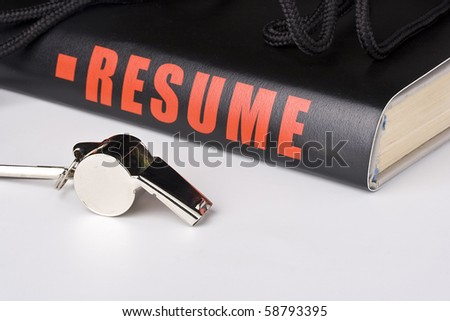 A silver whistle laying next to a very long resume. - stock photo