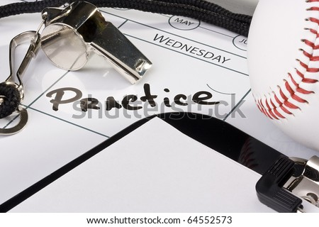 A silver whistle laying on a calendar next to a baseball and a clipboard, - stock photo