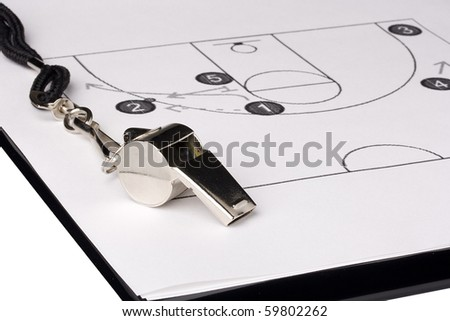 A silver whistle laying on a paper with the basketball game plan on it. - stock photo