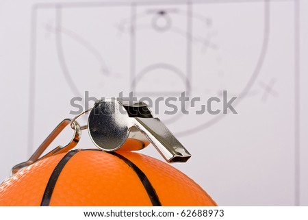 A silver whistle laying on an orange basketball in front of the game plan. - stock photo