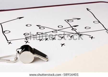 A silver whistle next to a drawing of a football play.
