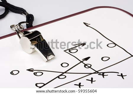 A silver whistle next to a drawing of a football play. - stock photo