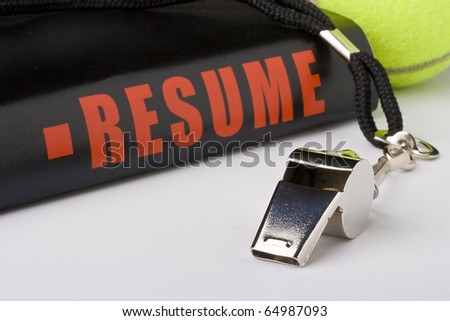 A silver whistle next to a tennis ball and a very long resume. - stock photo