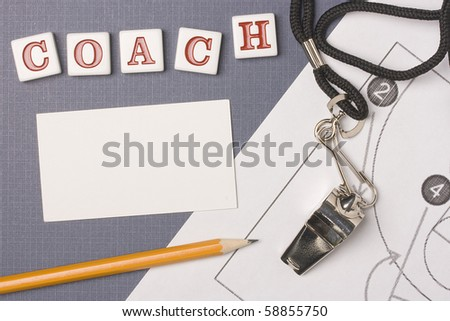 A silver whistle on a basketball diagram next to the word coach. Add your text to the white space. - stock photo