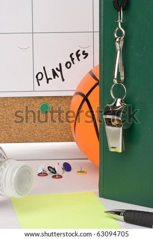A silver whistle on a green notebook next to a basketball and a calendar with the date of the playoffs on it. - stock photo