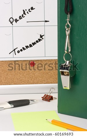 A silver whistle on a green notebook next to a schedule of the tournament. - stock photo